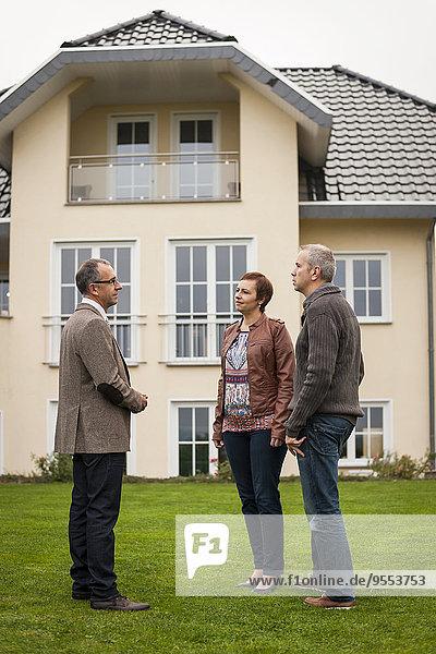Immobilienmakler kommuniziert mit potentiellen Käufern vor dem Wohnhaus