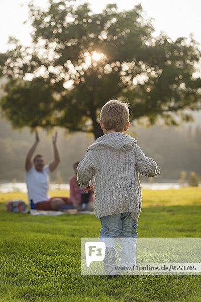 Junge rennt auf der Wiese zur Familie im Hintergrund