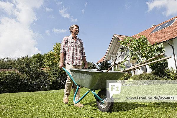 Mann mit Schubkarre im Garten