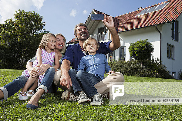 Happy family taking selfie in garden
