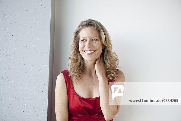 Porträt der lächelnden reifen Frau mit der Hand am Hals