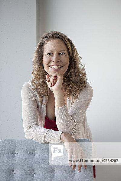 Porträt einer lächelnden reifen Frau mit Hand am Kinn