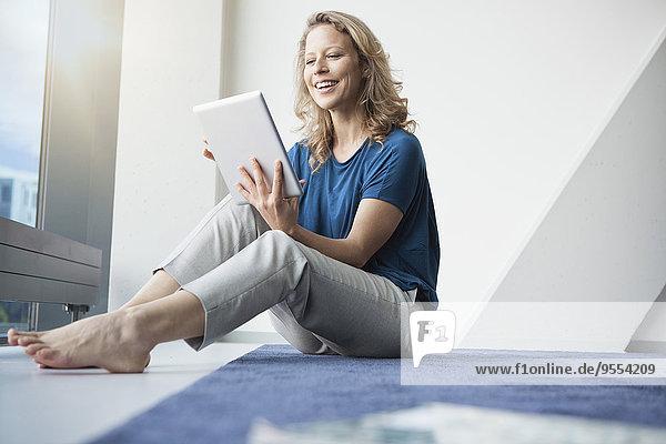 Porträt einer lächelnden reifen Frau  die mit einem digitalen Tablett auf dem Boden in ihrer Wohnung sitzt.