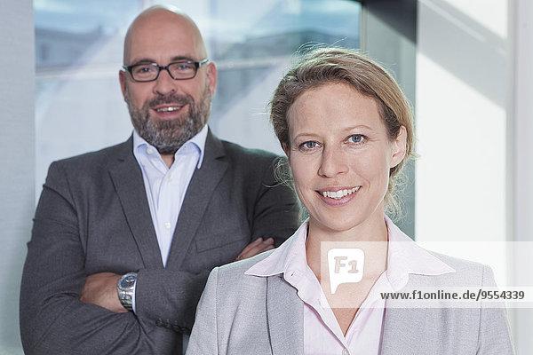 Porträt einer selbstbewussten Geschäftsfrau und eines Geschäftsmannes im Amt