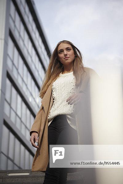 Porträt einer langhaarigen jungen Frau  die sich am Geländer lehnt