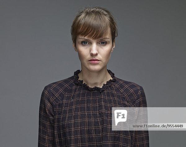 Porträt einer traurigen jungen Frau vor grauem Hintergrund