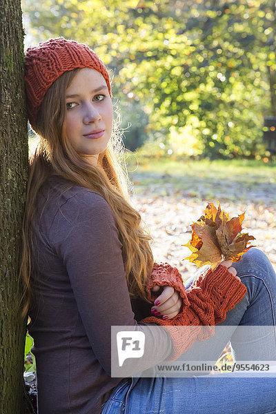 Porträt eines Teenagermädchens mit Wollmütze und Stulpen  die sich am Baum lehnen