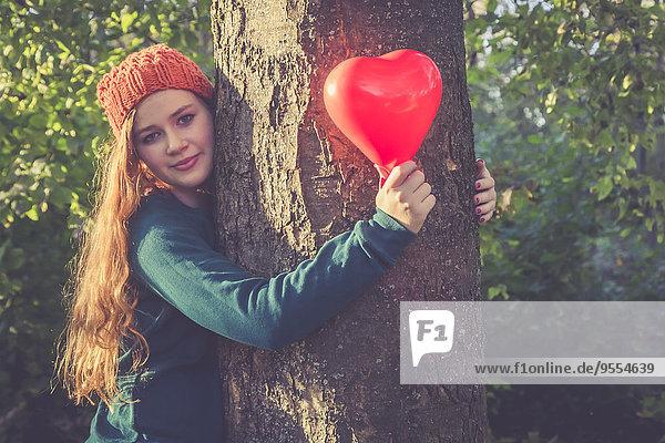 Porträt eines lächelnden Teenagermädchens mit herzförmigem Ballon an einem Baum