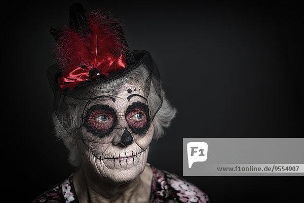 Porträt der Seniorin mit Zucker-Schädel-Make-up und schicker Mütze vor schwarzem Hintergrund