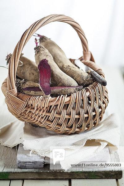 Drahtkorb aus geschnittenen und ganzen zylindrischen Rüben auf Stoff und Holzbrettern