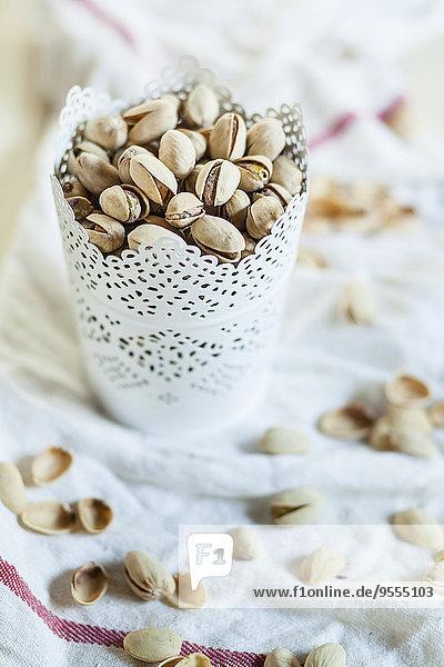 Tasse geröstete und gesalzene Pistazien auf Küchentuch