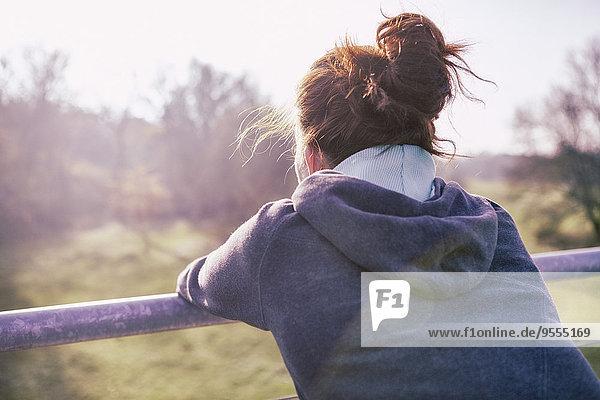 Junge Frau entspannt nach dem Joggen  Rückenansicht