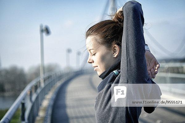 Junge Frau beim Stretching nach dem Joggen
