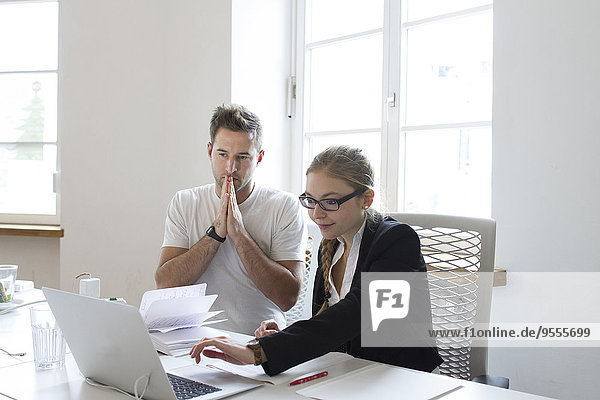 Junge Frau und Mann mit Laptop am Schreibtisch