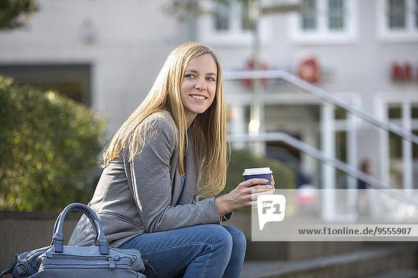 Lächelnde junge Frauen sitzen auf Stufen mit Kaffee zum Mitnehmen