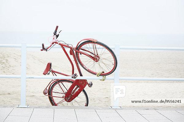 Niederlande  Scheveningen  roter holländischer Roadster an einem Geländer in Strandnähe befestigt