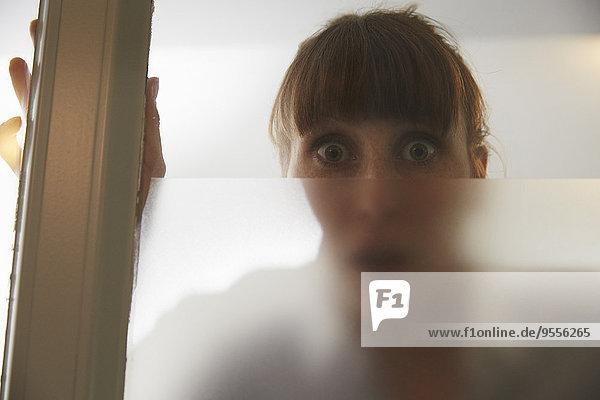 Verängstigte Frau hinter der Glasscheibe