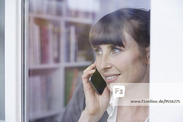 Frau hinter Glasscheibe am Handy