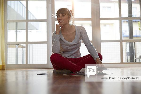 Frau auf dem Boden sitzend mit Magazin