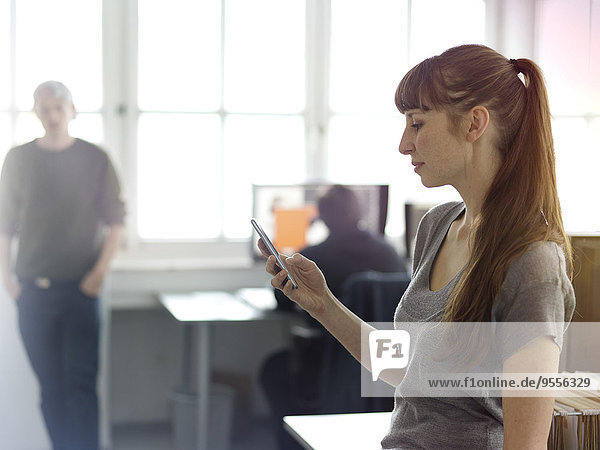 Woman in office looking at cell phone