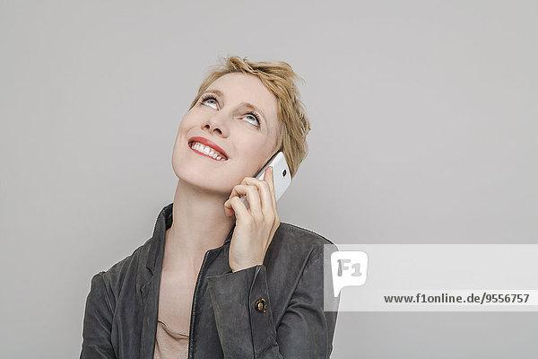 Porträt einer lächelnden blonden Frau beim Telefonieren mit dem Smartphone nach oben