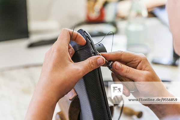 Woman in saddlery sewing hippotherapy belt
