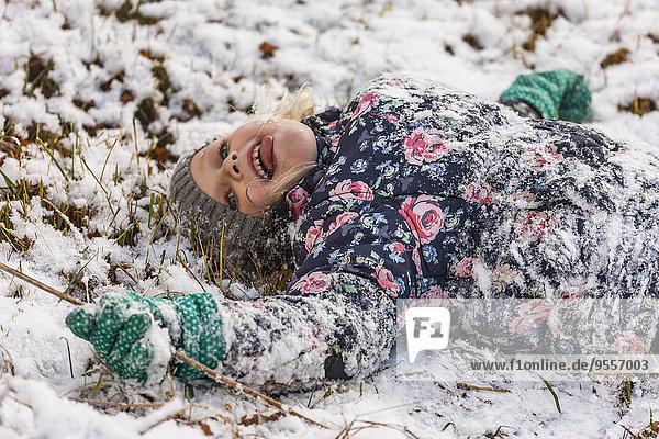 Kleines Mädchen mit ausgestreckter Zunge auf schneebedeckter Wiese liegend