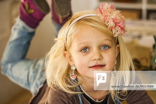 Portrait of blond little girl wearing earings and hair band
