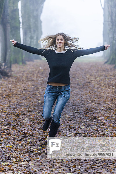 Woman with outstretched armes running along a forest track