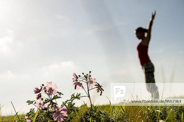 Silhouette der Frau auf der Wiese beim Turnen