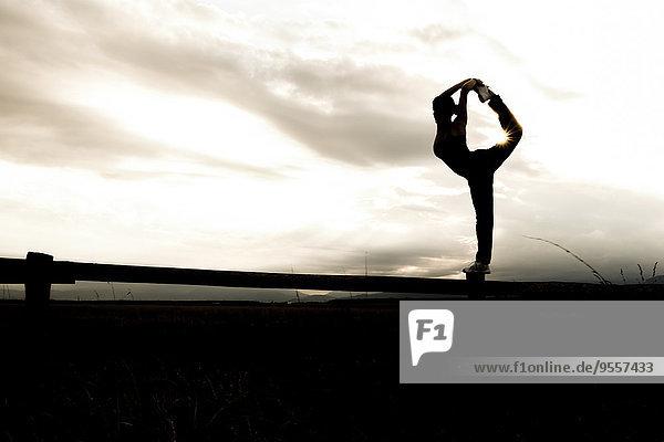 Silhouette einer jungen sportlichen Frau  die in der Dämmerung auf einem Bein auf einem Tor steht.