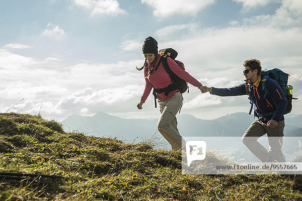 Austria  Tyrol  Tannheimer Tal  young couple hiking hand in hand on alpine meadow