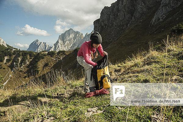 Österreich  Tirol  Tannheimer Tal  Wanderin mit Rucksack auf Bergwiese