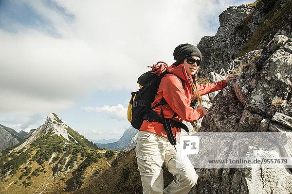 Österreich  Tirol  Tannheimer Tal  junge Frau beim Wandern auf Felsen