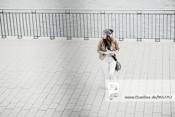 Junge Frau sitzt auf einem Poller an der Promenade und orientiert sich mit einem digitalen Tablett.