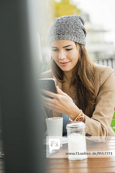 Lächelnde junge Frau sitzt auf dem Bürgersteig Cafe lesen SMS