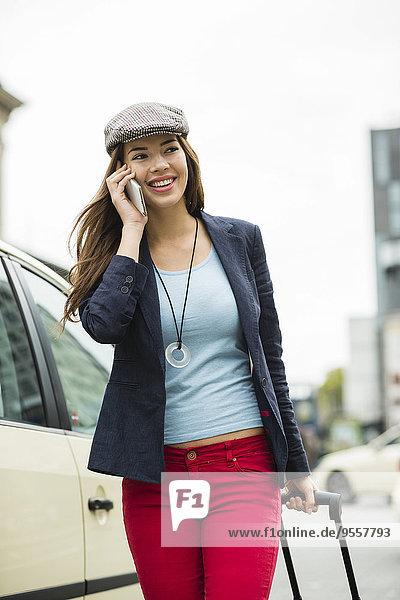 Porträt einer jungen lächelnden Frau mit Smartphone und Rollgepäck