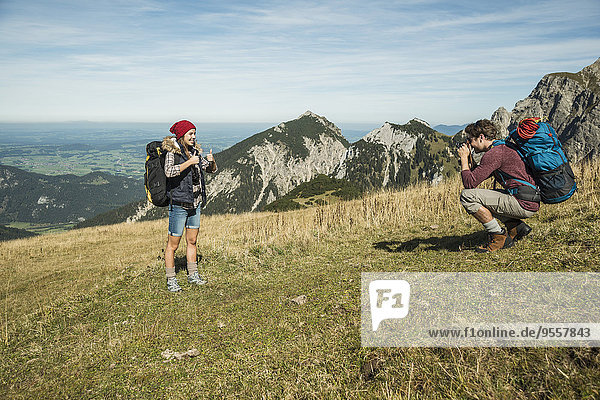 Austria  Tyrol  Tannheimer Tal  young man taking picture of girlfriend on alpine meadow