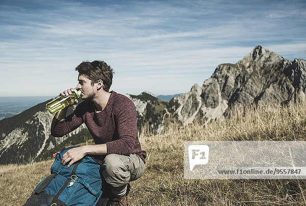 Austria  Tyrol  Tannheimer Tal  young man with backpack and drinking bottle on alpine meadow