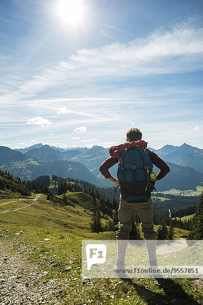 Austria  Tyrol  Tannheimer Tal  young man in mountains looking at view