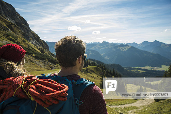 Austria  Tyrol  Tannheimer Tal  young couple in mountains looking at view