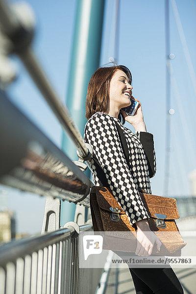 Deutschland  Frankfurt  junge Frau auf der Brücke per Handy