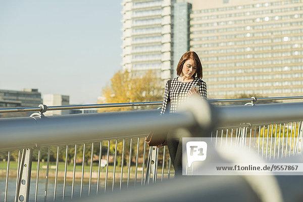 Deutschland  Frankfurt  junge Geschäftsfrau mit Handy auf Brücke