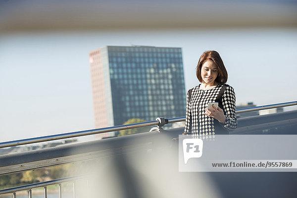 Deutschland  Frankfurt  junge Geschäftsfrau auf Brücke mit Handy