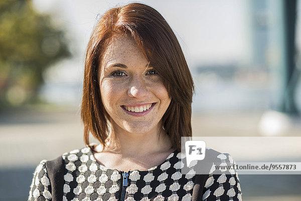 Porträt der lächelnden brünetten jungen Frau im Freien