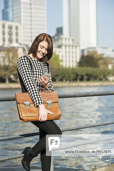 Deutschland  Frankfurt  junge Geschäftsfrau am Flussufer mit Handy