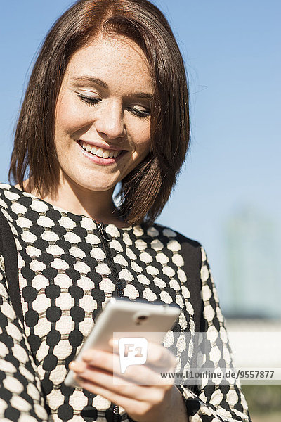 Lächelnde junge Frau auf dem Handy