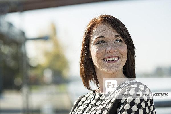 Lächelnde brünette junge Frau im Freien