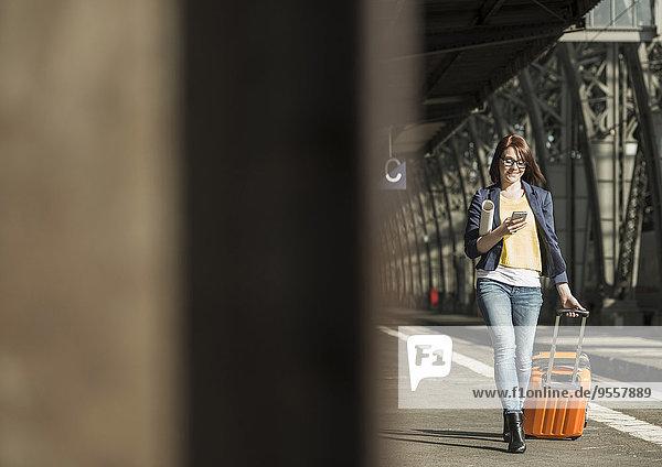 Junge Frau mit Handy und Gepäck am Bahnhof