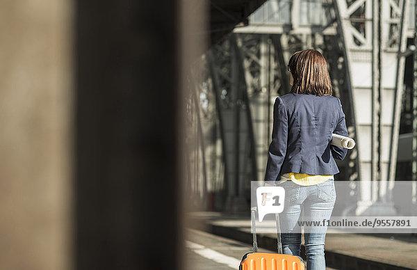 Junge Frau mit Gepäck am Bahnhof